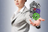 Business woman holds up a mechanism — Stockfoto