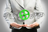 Business woman holds up a mechanism of gears — Stockfoto