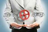 Business woman holds up a mechanism of gears — Foto de Stock