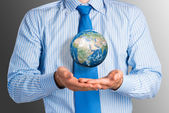 Businessman holds up an Earth — Stock Photo