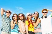 Grupp ungdomar som bär solglasögon och hatt — Stockfoto