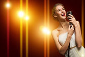 Attractive female singer with microphone — Stock Photo