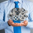 Business man holds up a mechanism of gears — Stock Photo