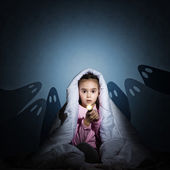 Girl under the covers with a flashlight — Stock Photo