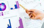 Ręka wskazując ołówek na wykresach finansowych — Zdjęcie stockowe