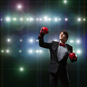 Businessman with boxing gloves in the ring — Stok fotoğraf