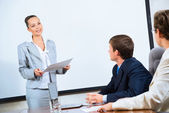 Discusses business woman with colleagues — Stock Photo