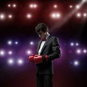 Businessman with boxing gloves in the ring — Stockfoto
