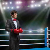 Businessman with boxing gloves in the ring — Zdjęcie stockowe