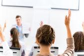 Female hand raised in class — Stock Photo