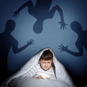 Boy under the covers with a flashlight — Stok fotoğraf