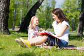 Reading a book in the summer park — Stock Photo