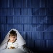 Boy under the covers with a flashlight — Stock Photo