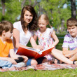 Teacher reads a book to children in a summer park — Stock Photo