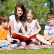 Teacher reads a book to children in a summer park — Stock Photo #44793161