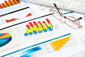 Glasses, business papers with charts — Stock Photo