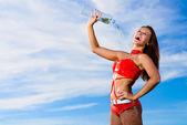 Ragazza sportiva in rosso uniforme con una bottiglia di acqua — Foto Stock