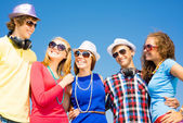 Group of young people wearing sunglasses and hat — Stock Photo