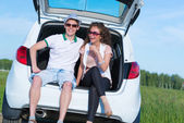 Young couple sitting in the open trunk — Stock Photo