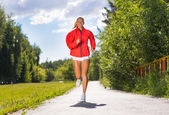 Young athletic woman running on the road — Foto Stock