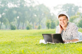 Ung man arbetar i parken med en bärbar dator — Stockfoto