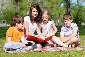 Teacher reads a book to children in a summer park — Stock Photo
