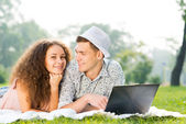 Couple lying together in a park with laptop — Stock Photo