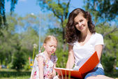Girl and a young woman reading a book together — Fotografia Stock