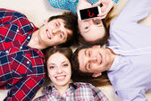 Four young men lie together — Stock Photo