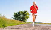 Young athletic woman running on the road — Stock Photo