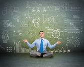 Business man meditating on floor — Stock Photo