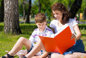 Son and mother reading book together — Stock Photo