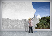 Girl paints the wall — Stock Photo