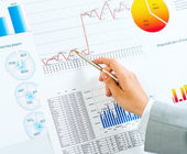 Hand pointing on financial charts — Stock Photo