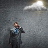 Businessman standing in rays of light — Stock Photo