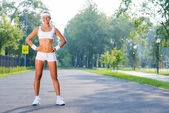 Sport woman standing in sunny park — Stock Photo