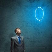 Businessman looking up at balloon — Stock Photo