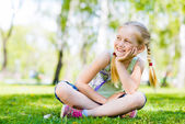Flicka sitter i gräset — Stockfoto