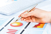 Hand pointing to the financial chart — Stock Photo