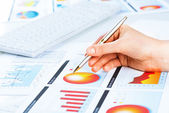 Hand pointing to financial chart — Stock Photo