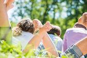 Glückliche familie im park liegen — Stockfoto