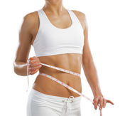 Young athletic woman measuring waist — Stock Photo