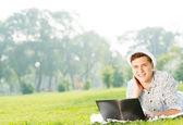 Homem trabalhando no parque com laptop — Fotografia Stock
