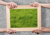 Hands holding wooden frame — Stock Photo