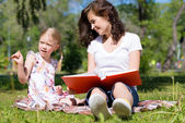 Girl and woman reading a book — Stock Photo