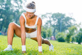Fitness girl stretching in park — Stock Photo