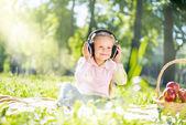 Dívka v letním parku poslech hudby — Stock fotografie