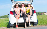 Women sitting in open trunk — Stock Photo