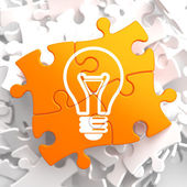 Light Bulb Icon on Orange Puzzle. — Stock Photo
