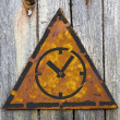 Stock Photo: Icon of Clock Face on Rusty Warning Sign.
